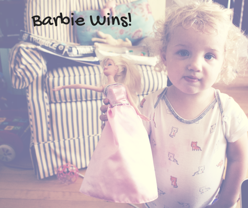 Image of a toddler holding a barbie doll