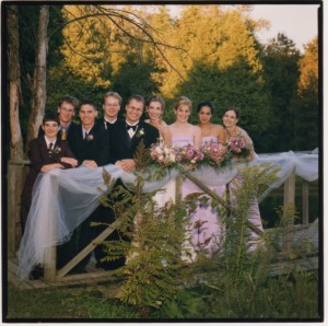 Wedding photo of a wedding party standing on a wooden bridge