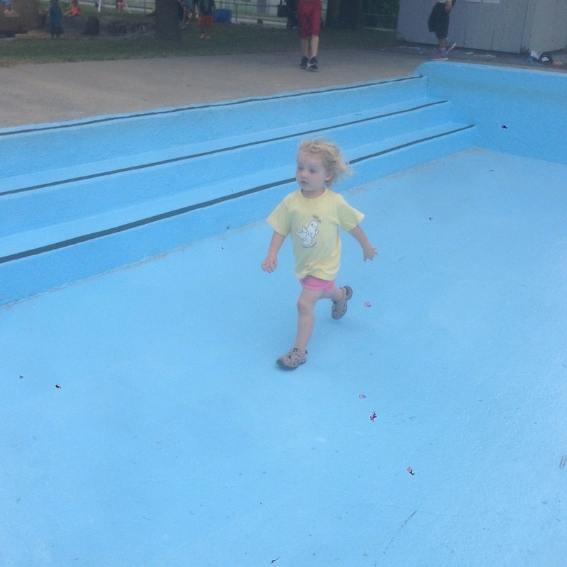 Image of a girl running in an empty wading pool
