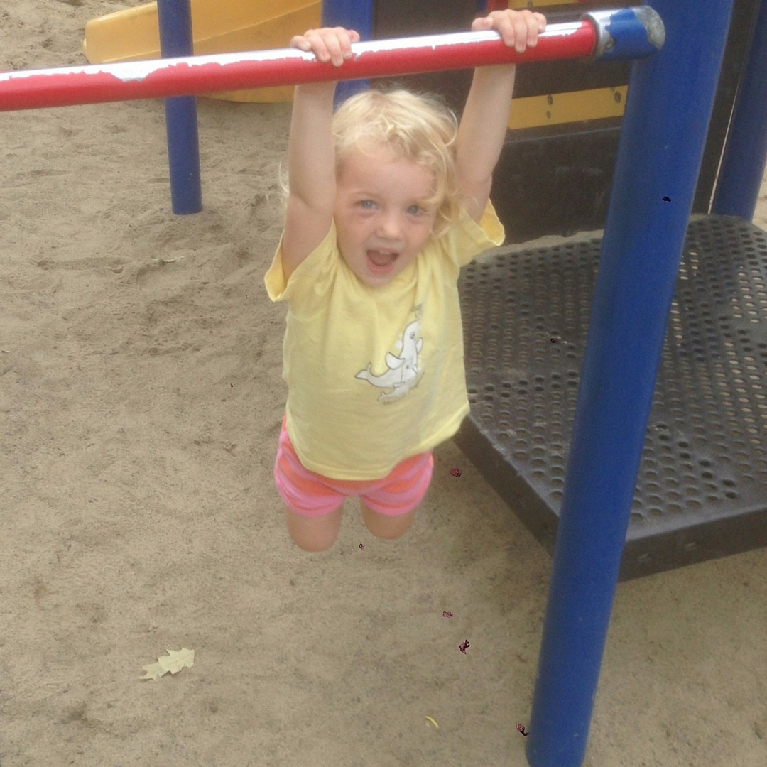 Image of a girl swinging on a metal bar