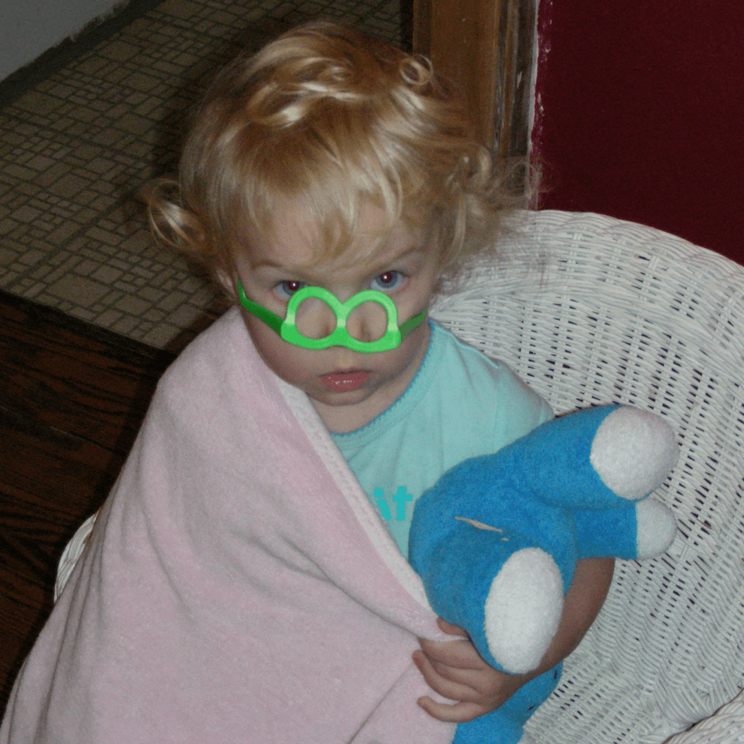Image of a girl wearing upside down green toy glasses and carrying a blue bear